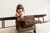 Cute Baby Pilot In The Helmet Sitting In The Wooden Airplane poster