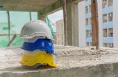 White, Yellow And Blue Hard Safety Helmet For Safety Accident Stack On Floor At Workplace In Constru poster