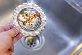 Hand Holding Kitchen Sink Waste Filter With Trapped Food Waste, Against Sink Background poster