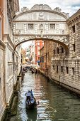 Gondola With Tourists Sails On Old Canal Under Medieval Bridge Of Sighs, Venice, Italy. Famous Histo poster