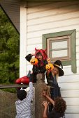 Group Of Four Sneaky Kids Climbing Fence While Trick Or Treating On Halloween, Copy Space poster