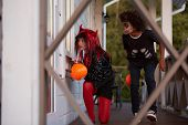 Portrait Of Two Sneaky Kids Hiding Outside House While Playing Games On Halloween, Copy Space poster