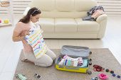 Holidays, Voyage And Travel Concept - Young Woman Packs A Suitcase At Home In The Bedroom, A Lot Of  poster