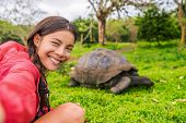 Galapagos Adventure travel tourist on Galapagos Islands taking selfie photo by Giant Tortoises on Sa poster