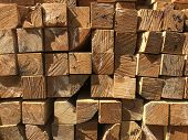 Stack Of Lumber At The Outdoor Warehouse. Stacked Wooden Beams Of Square Section poster