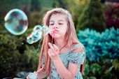 Beautiful Little Girl Child. Outdoors, Blowing Bubbles. Childrens Lifestyle poster