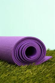 stock photo of yoga mat  - Purple Yoga Exercise Mat On Green Grass - JPG
