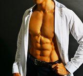 foto of nipple  - Muscular and tanned male torso isolated on black background - JPG