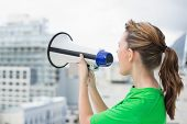 Side view of woman using and screaming in megaphone