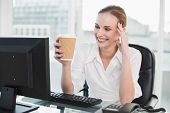 Smiling businesswoman holding disposable cup sitting at desk in her office