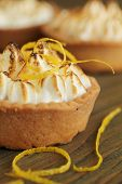 Close up of a lemon tart with lemon zest on a wooden table