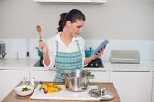 Focused gorgeous woman wearing apron using tablet while cooking in bright kitchen
