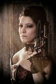 foto of bustiers  - a woman in steampunk outfit holding a gun and looking into the camera in front of a wooden background - JPG