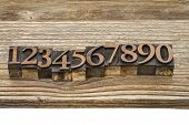 number abstract in vintage letterpress wood type against grained wooden plank