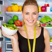 stock photo of cheers  - Closeup portrait of beautiful cheerful girl holding in hand bowl with fresh tasty green salad - JPG