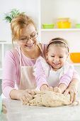 Happy Little Girl With Grandmother In The Kitchen
