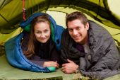 stock photo of sleeping bag  - A happy couple in a tent looking at the camera - JPG