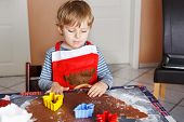 picture of ginger bread  - Cute little child baking ginger bread cookies for Christmas in home - JPG