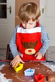 stock photo of ginger bread  - Little boy baking ginger bread trees for Christmas in home - JPG