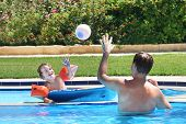 stock photo of pool ball  - Father And Son Playing Ball In A Swimming Pool - JPG