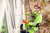 stock photo of insulator  - Industrial climber placing a polyfoam sheet insulation to wall of a building - JPG