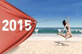picture of pulling  - Attractive young woman wearing bikini jumping on beach while pulling a banner new year 2015 - JPG