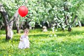 foto of christening  - Beautiful Little Girl Playing With A Red Balloon In An Apple Tree Garden - JPG