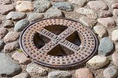 picture of manhole  - Old steel sewer manhole on the cobblestone road - JPG