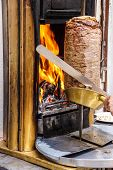 stock photo of kababs  - Cook slices shawarma from the spit for doner kababs in Mardin Turkey - JPG