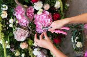 pic of card-making  - Florist at work. Woman making spring floral decorations the wedding table the bride and groom.