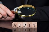 stock photo of financial audit  - Midsection of young businessman examining Audit blocks through magnifying glass on desk - JPG