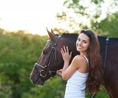 Portrait beautiful woman with long hair next horse pic.