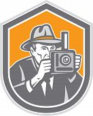 stock photo of fedora  - Illustration of a photographer wearing fedora hat shooting with vintage bellows camera set inside shield crest on isolated background done in retro style - JPG