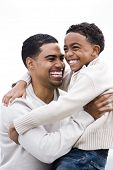 Happy African-American dad hugging son