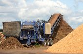 picture of chute  - A portable wood chipper mulches wood by products into sawdust used for fertilizer - JPG