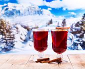 picture of apr  - glasses of mulled wine on wooden table over winter landscape