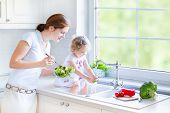 pic of window washing  - Young Beautiful Mother And Her Cute Curly Toddler Daughter Washing Vegetables Together In A Kitchen