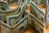 pic of twenty dollar bill  - close up of a few 20 dollar bills standing on their sides on a wooden table - JPG