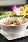pic of crispy rice  - Closeup of a person eating Thai style crispy pork rice noodle soup from a bowl with chopsticks - JPG
