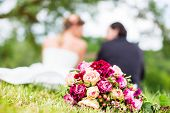 stock photo of candid  - Wedding couple of bride and groom sitting on the meadow with bridal bouquet behind them - JPG