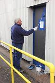pic of roller door  - A painter painting a door using a gloss roller - JPG
