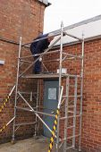 foto of scaffold  - A painter working from a scaffold tower - JPG