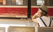 stock photo of passenger train  - Young cute girl waiting for the train at the railway station - JPG