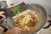 picture of scallion  - Adding scallion into the fried rice while stirring it with spatula - JPG
