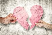 picture of broken hearted  - Couple holding two halves of broken heart against grey background - JPG