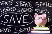 stock photo of untidiness  - Pink piggy bank with glasses standing on books next to a blackboard with untidy spending and saving message - JPG