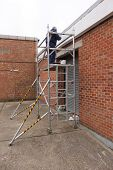 stock photo of scaffold  - A painter working from a scaffold tower - JPG