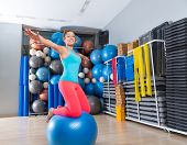 stock photo of open arms  - Girl at gym swiss ball knee balance drill exercise workout open arms - JPG