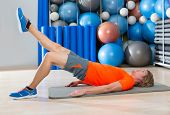 stock photo of gym workout  - hip lift with leg extension blond man at gym workout with swiss ball background - JPG