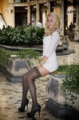 picture of posh  - Elegant pretty blonde young woman sitting in white dress in posh city setting in Europe - JPG